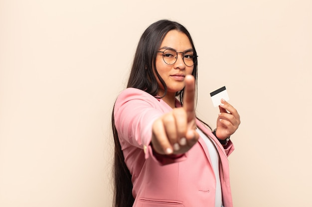 Jeune femme latine souriante fièrement et avec confiance faisant triomphalement la pose numéro un, se sentant comme un leader