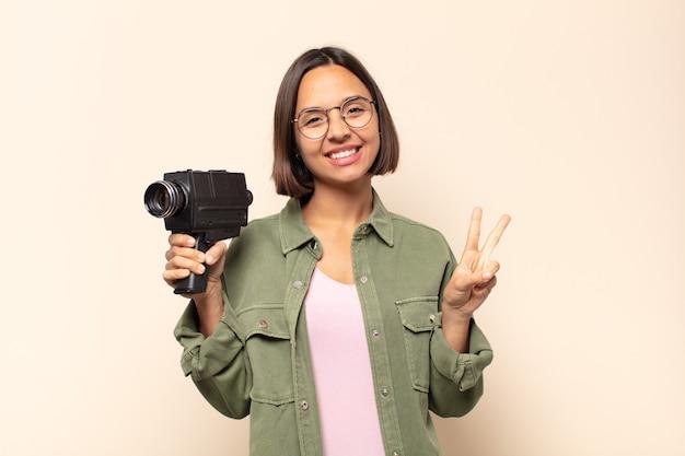 Jeune femme latine souriante et à la recherche heureuse, insouciante et positive, gestes de victoire ou de paix d'une seule main