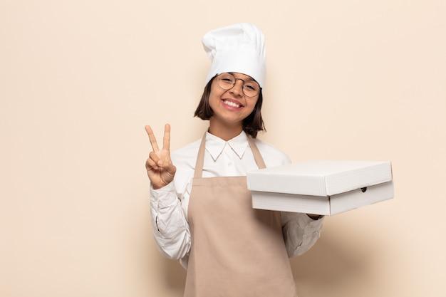Jeune femme latine souriante et semblant amicale, montrant le numéro deux ou la seconde avec la main vers l'avant, compte à rebours