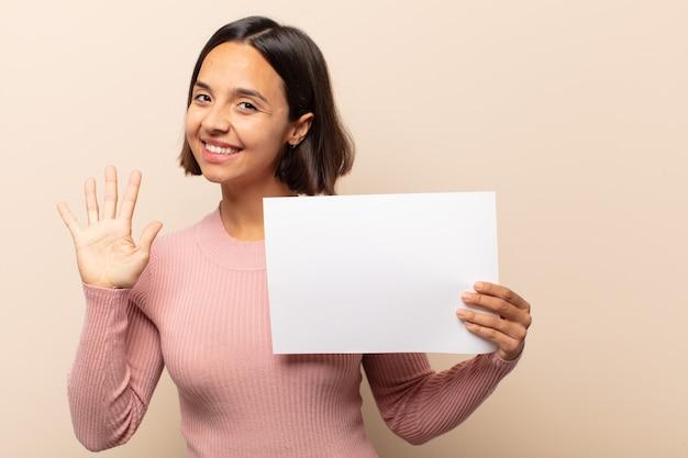 Jeune femme latine souriante et à la sympathique, montrant le numéro cinq ou cinquième avec la main en avant, compte à rebours