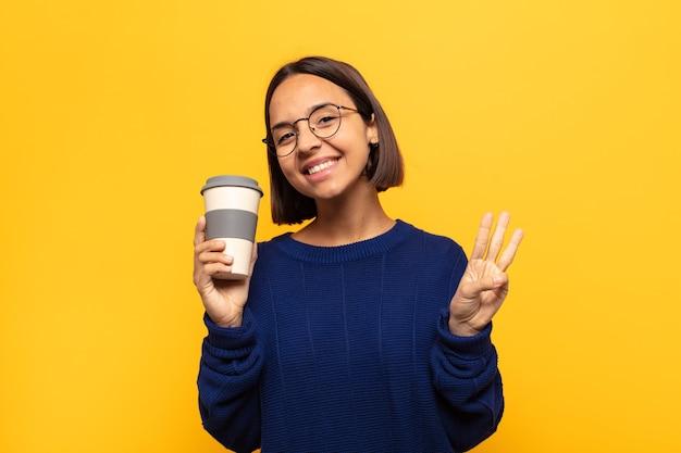 Jeune femme latine souriante et à la sympathique, montrant le numéro trois ou troisième avec la main en avant, compte à rebours