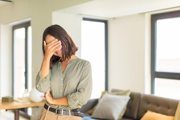 Jeune femme latine à stressé, honteux ou contrarié, avec un mal de tête, couvrant le visage avec la main