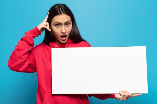 Jeune femme latine à la surprise, la bouche ouverte, choquée, réalisant une nouvelle pensée, idée ou concept