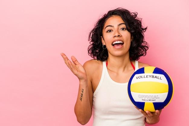 Jeune femme latine tenant un ballon de volley isolé sur fond rose montrant un espace de copie sur une paume et tenant une autre main sur la taille.
