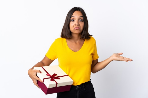 Jeune femme latine tenant un cadeau isolé sur fond blanc ayant des doutes tout en levant les mains