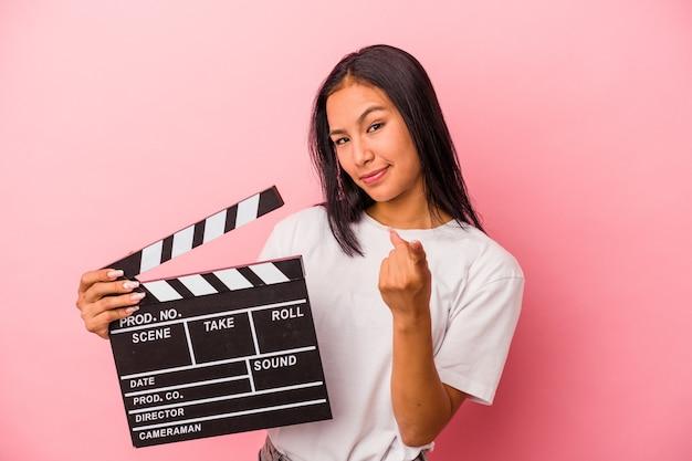 Jeune femme latine tenant un clap isolé sur fond rose pointant du doigt vers vous comme si vous vous invitiez à vous rapprocher.