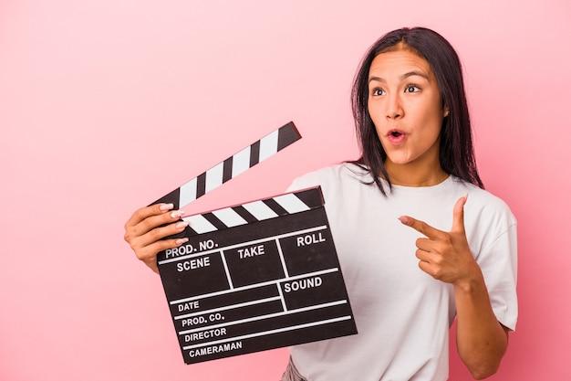 Jeune femme latine tenant un clap isolé sur fond rose pointant vers le côté