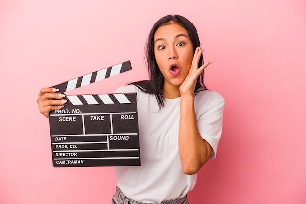 Jeune femme latine tenant un clap isolé sur fond rose surpris et choqué.