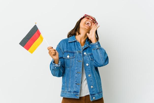 Jeune femme latine tenant un drapeau allemand isolé sur fond blanc criant excité à l'avant.