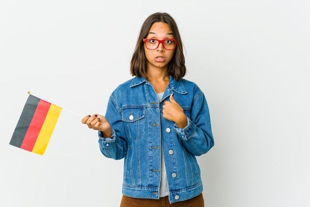 Jeune femme latine tenant un drapeau allemand isolé sur un mur blanc surpris de pointer avec le doigt, souriant largement.