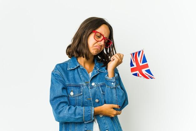 Jeune femme latine tenant un drapeau anglais isolé sur le coude de massage mur blanc, souffrant après un mauvais mouvement.