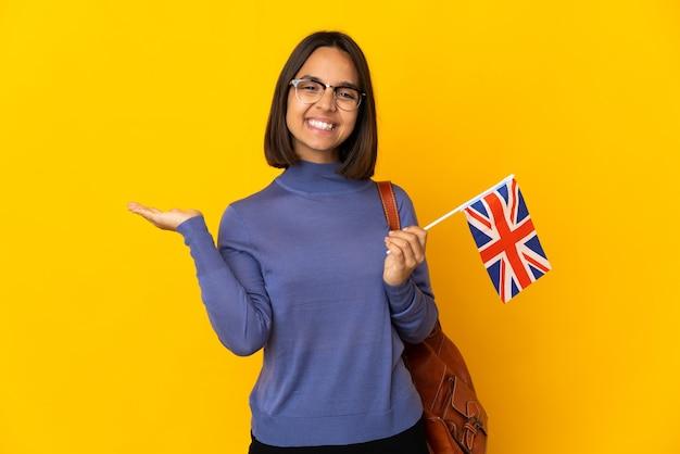 Jeune femme latine tenant un drapeau du royaume-uni isolé sur un mur jaune affichant copyspace sur la paume pour insérer une annonce et avec les pouces vers le haut