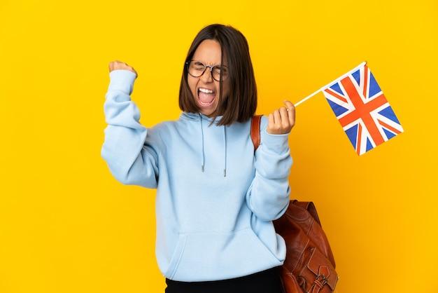 Jeune femme latine tenant un drapeau du royaume-uni isolé sur un mur jaune célébrant une victoire