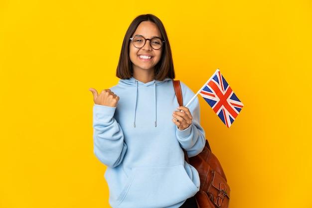 Jeune femme latine tenant un drapeau du royaume-uni isolé sur un mur jaune pointant vers le côté pour présenter un produit