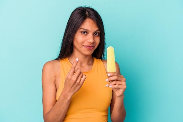 Jeune femme latine tenant une glace isolée sur fond bleu pointant du doigt vers vous comme si vous vous invitiez à vous rapprocher.
