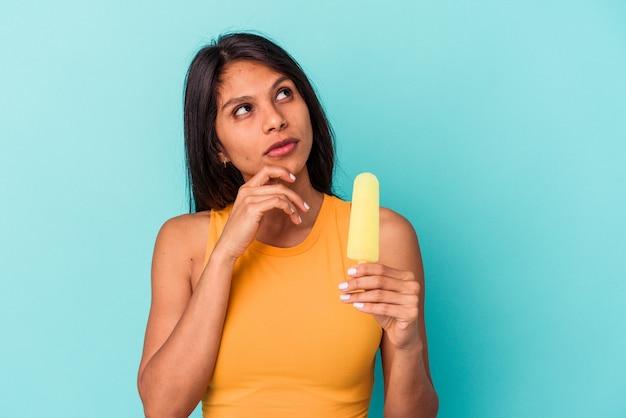 Jeune femme latine tenant une glace isolée sur fond bleu regardant de côté avec une expression douteuse et sceptique.