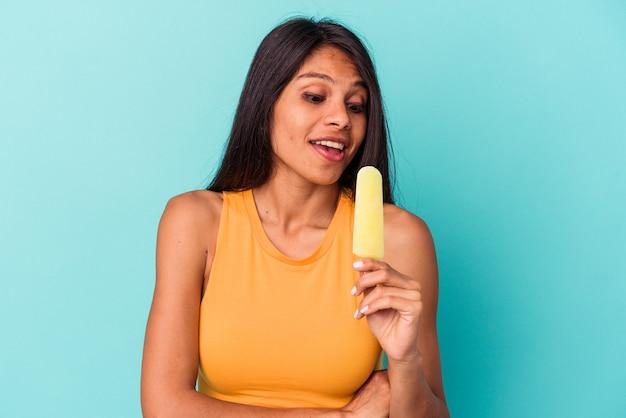 Jeune femme latine tenant une glace isolée sur fond bleu