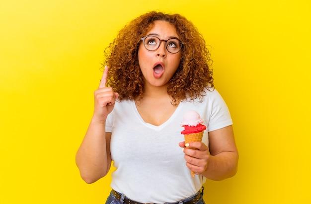 Jeune femme latine tenant une glace isolée sur un mur jaune pointant vers le haut avec la bouche ouverte