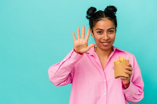 Jeune femme latine tenant des jetons isolés sur fond bleu souriant joyeux montrant le numéro cinq avec les doigts.