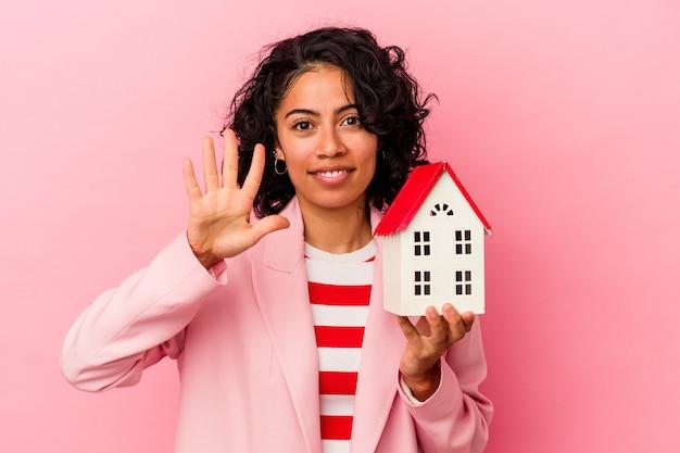 Jeune femme latine tenant une maison de jouet isolée sur fond rose souriante joyeuse montrant le numéro cinq avec les doigts.
