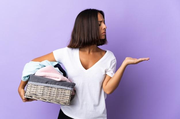 Jeune femme latine tenant un panier de vêtements isolé sur fond violet tenant avec des doutes