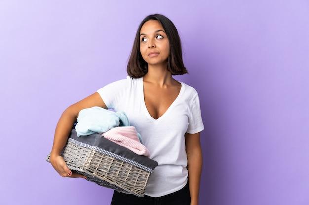 Jeune femme latine tenant un panier de vêtements isolé sur violet ayant des doutes tout en regardant côté