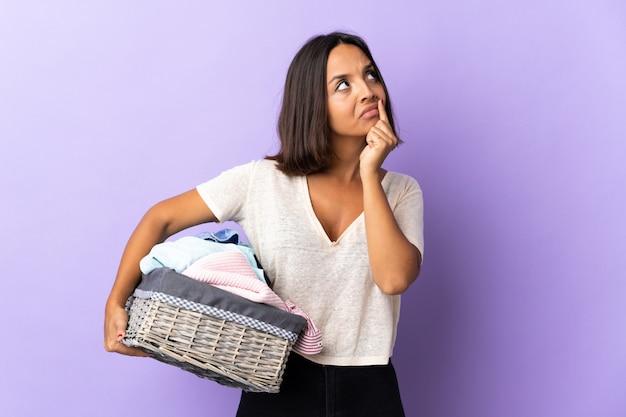 Jeune femme latine tenant un panier de vêtements isolé sur violet ayant des doutes tout en regardant