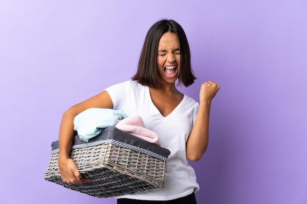 Jeune femme latine tenant un panier de vêtements isolé sur violet célébrant une victoire