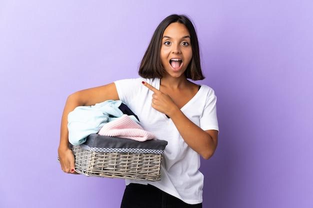 Jeune femme latine tenant un panier de vêtements isolé sur violet côté surpris et pointant