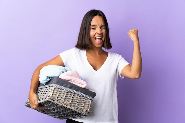 Jeune femme latine tenant un panier de vêtements isolé sur violet faisant un geste fort