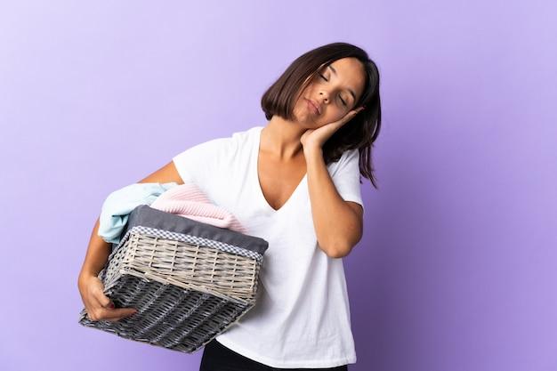 Jeune femme latine tenant un panier de vêtements isolé sur violet faisant le geste de sommeil dans une expression dorable