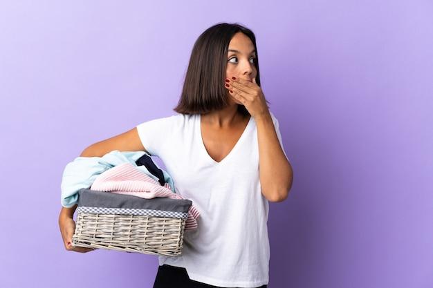 Jeune femme latine tenant un panier de vêtements isolé sur violet faisant un geste de surprise tout en regardant sur le côté