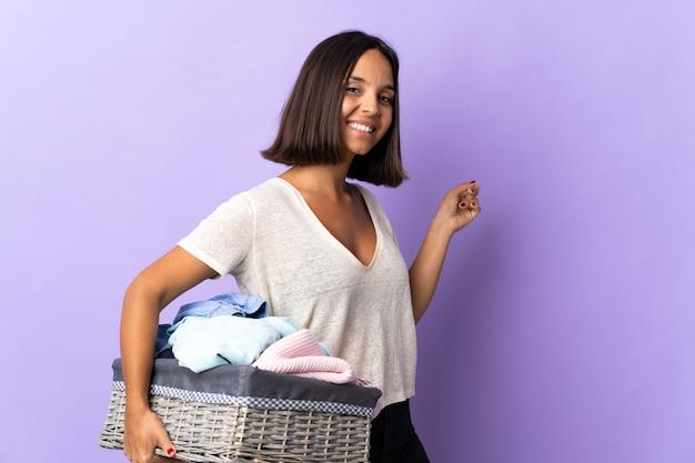 Jeune femme latine tenant un panier de vêtements isolé sur violet pointant vers l'arrière