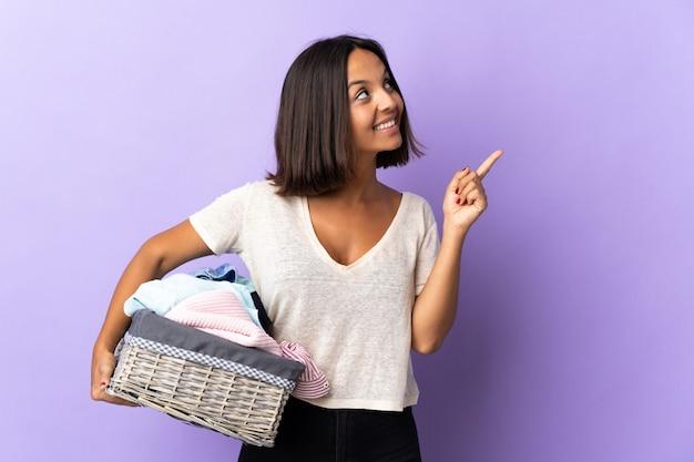 Jeune femme latine tenant un panier de vêtements isolé sur violet pointant vers le haut une excellente idée