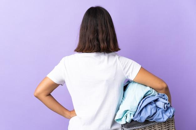 Jeune femme latine tenant un panier de vêtements isolé sur violet en position arrière