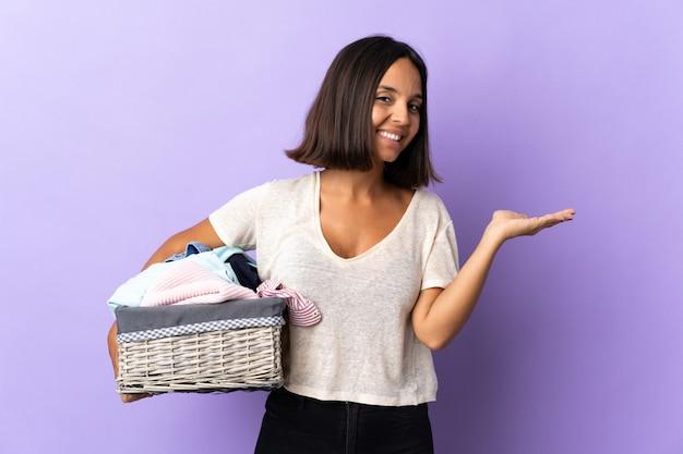 Jeune femme latine tenant un panier de vêtements isolé sur violet présentant une idée tout en regardant en souriant vers