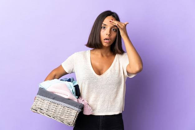 Jeune femme latine tenant un panier de vêtements isolé sur violet a réalisé quelque chose et l'intention de la solution