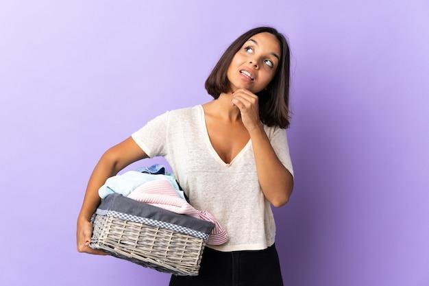 Jeune femme latine tenant un panier de vêtements isolé sur violet regardant en souriant
