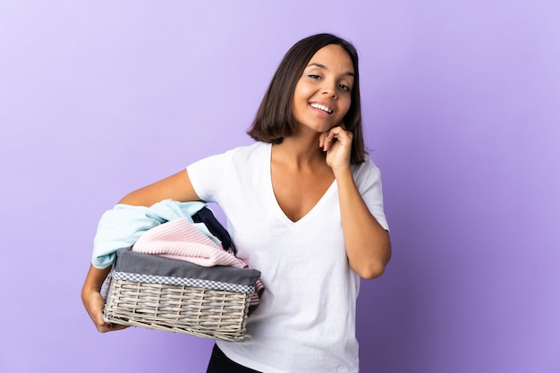 Jeune femme latine tenant un panier de vêtements isolé sur violet en riant