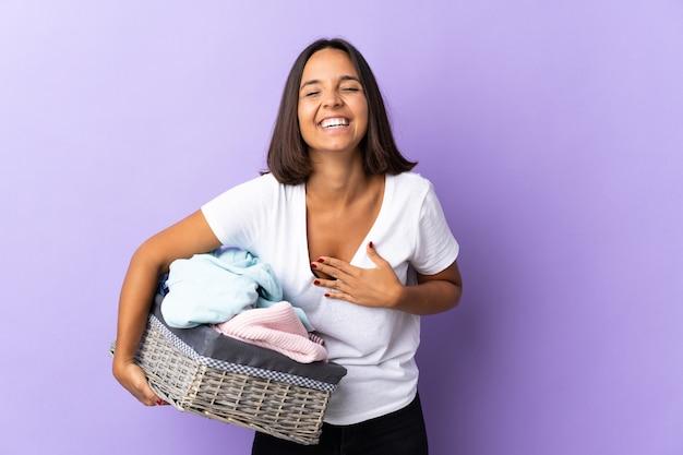 Jeune femme latine tenant un panier de vêtements isolé sur violet souriant beaucoup