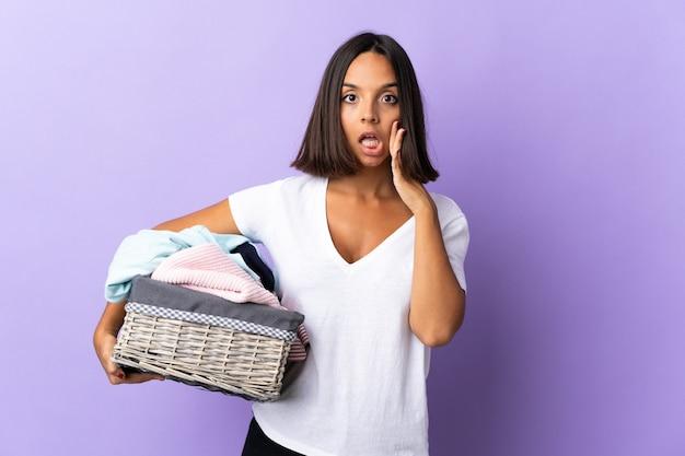 Jeune femme latine tenant un panier de vêtements isolé sur violet avec surprise et expression du visage choqué