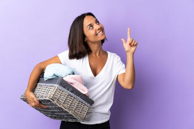 Jeune femme latine tenant un panier de vêtements