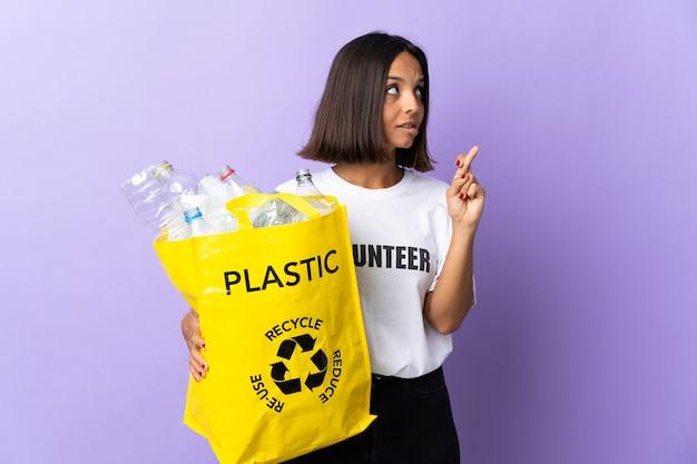 Jeune femme latine tenant un sac de recyclage plein de papier à recycler