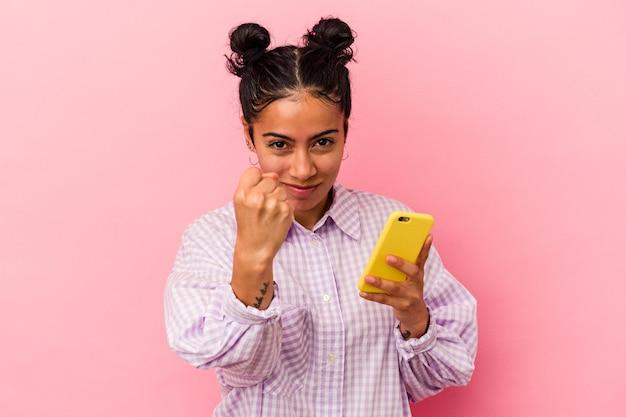 Jeune femme latine tenant un téléphone mobile isolé sur fond rose montrant le poing à la caméra, expression faciale agressive.