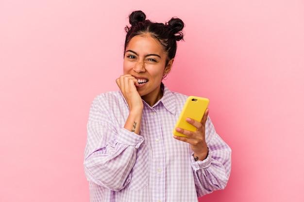 Jeune femme latine tenant un téléphone portable isolé sur fond rose se rongeant les ongles, nerveuse et très anxieuse.