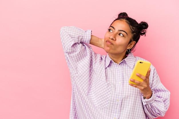 Jeune femme latine tenant un téléphone portable isolé sur fond rose touchant l'arrière de la tête, pensant et faisant un choix.