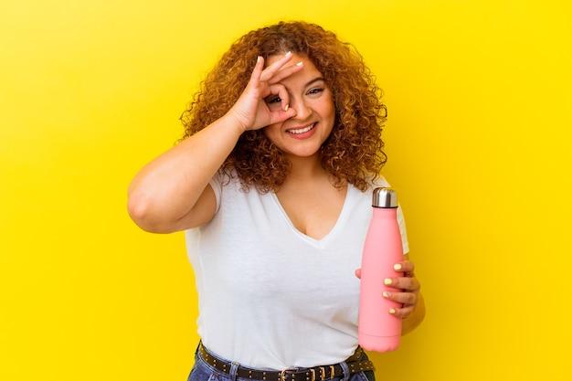 Jeune femme latine tenant un thermos isolé sur fond jaune excité en gardant le geste ok sur les yeux.