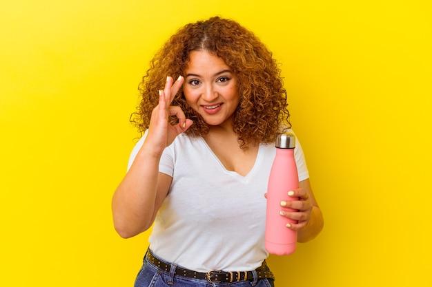 Jeune femme latine tenant un thermos isolé sur fond jaune joyeux et confiant montrant le geste ok.