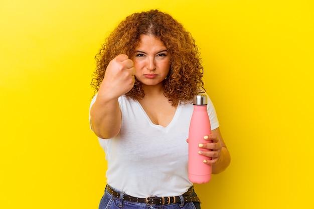 Jeune femme latine tenant un thermos isolé sur mur jaune montrant le poing à l'avant, expression faciale agressive