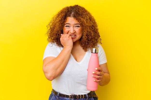 Jeune femme latine tenant un thermos isolé sur mur jaune se ronger les ongles, nerveux et très anxieux